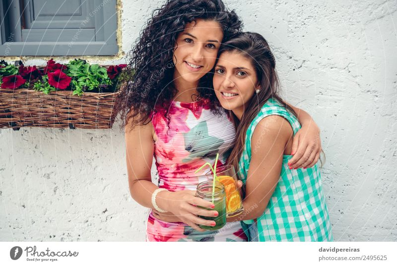 Two women with beverages looking at camera embracing Vegetable Fruit Beverage Juice Lifestyle Joy Happy Leisure and hobbies Summer Human being Woman Adults