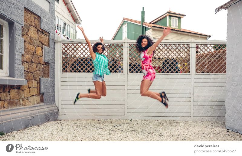 Happy women jumping in front of garden fence Lifestyle Joy Leisure and hobbies Summer Garden Human being Woman Adults Friendship Arm Brunette Wood To enjoy