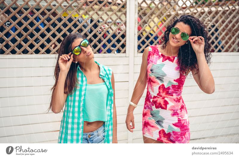 Women with sunglasses looking at camera over garden fence Lifestyle Joy Happy Face Leisure and hobbies Summer Garden Mirror Human being Woman Adults Friendship