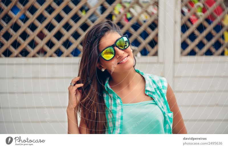 Woman with sunglasses looking at camera over garden fence Lifestyle Joy Happy Beautiful Face Leisure and hobbies Summer Garden Mirror Human being Adults Fingers