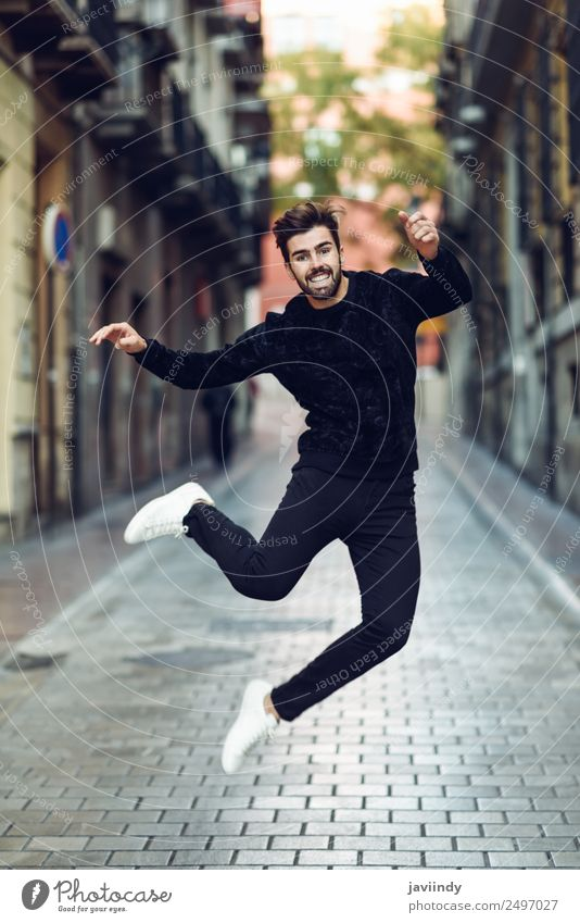 Young bearded man jumping in urban street Lifestyle Joy Human being Masculine Young man Youth (Young adults) Man Adults 1 18 - 30 years Street Fashion Sweater