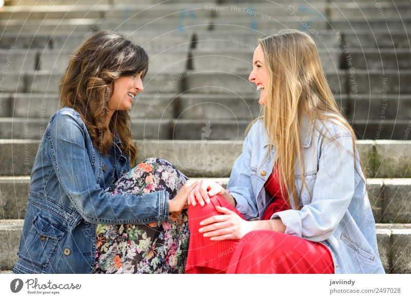 Two young women talking and laughing outdoors Lifestyle Style Joy Happy Beautiful To talk Human being Feminine Young woman Youth (Young adults) Woman Adults