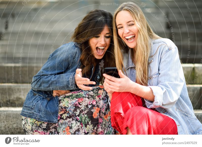 Two women laughing looking at their smart phone Woman Human being Youth (Young adults) Young woman Beautiful White Joy 18 - 30 years Street Adults Lifestyle