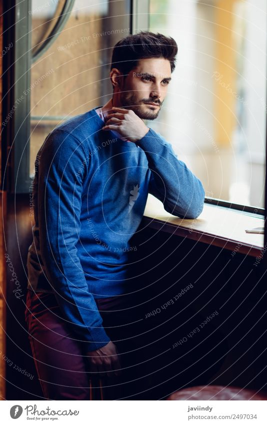 Thoughtful man with blue sweater with lost look near a window in a modern pub. Bearded guy with modern hairstyle Lifestyle Style Beautiful Hair and hairstyles