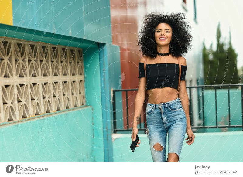 Young black woman with afro hair walking outdoors Lifestyle Style Joy Beautiful Hair and hairstyles Telephone Human being Feminine Young woman