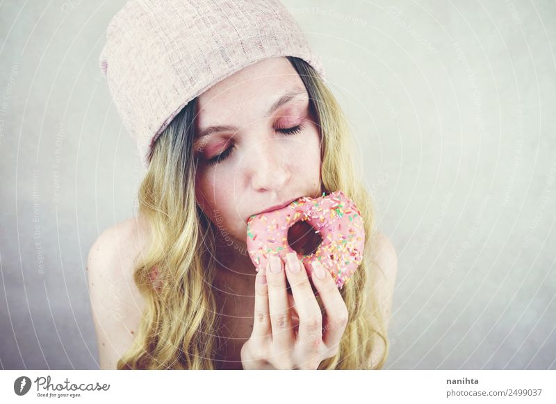 Young woman eating a pink donut Food Candy Donut Eating Fast food Lifestyle Style Design Joy Beautiful Hair and hairstyles Human being Feminine