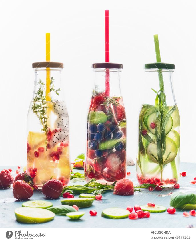 Infused water in bottles with drink straw and ingredients on white background, front view. Water Flavored with fruits, berries and herbs. Summer drinks. Healthy and clean detox beverages.