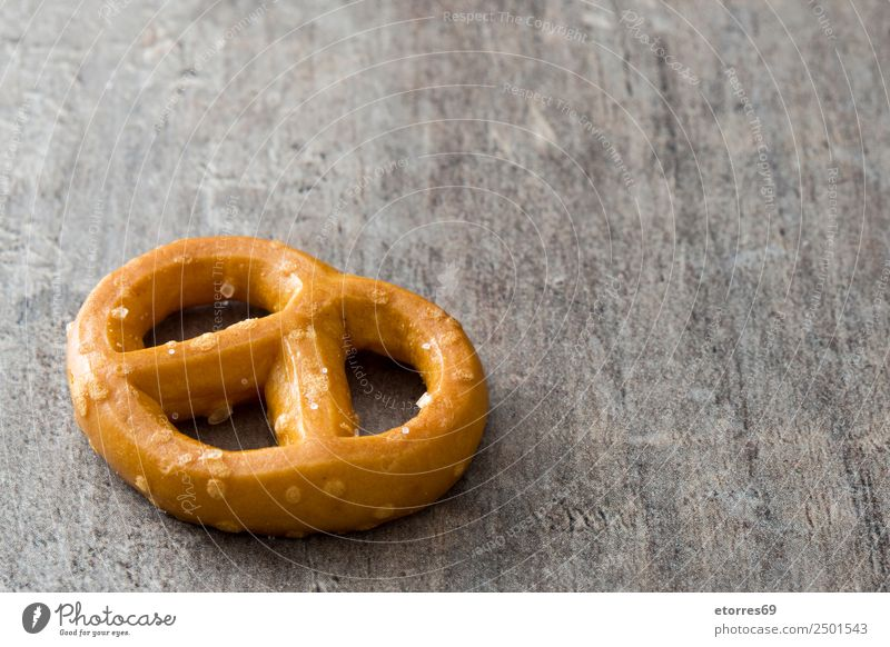 Salted pretzel on wooden background Food Bread Cooking oil Nutrition Eating Breakfast Lunch Vegetarian diet Diet Oktoberfest Wood Brown Pretzel Food photograph