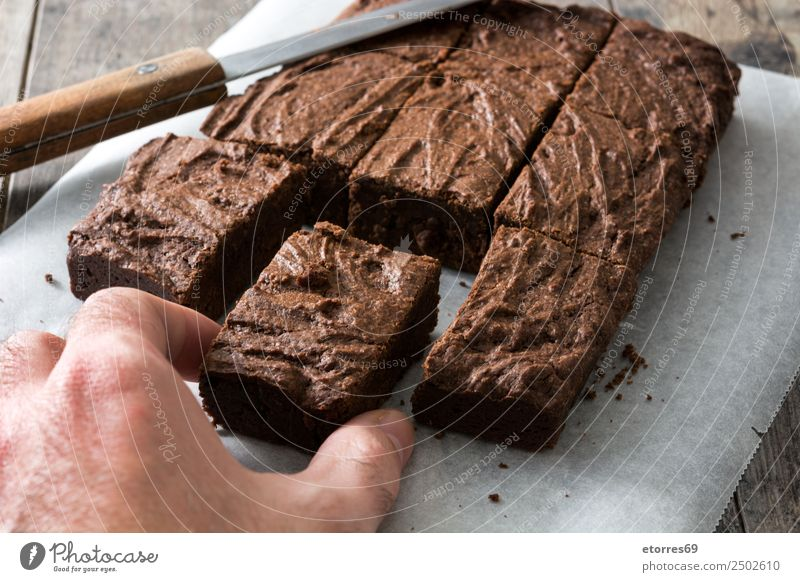 Hand catching a chocolate brownie portion Food Dessert Candy Chocolate Nutrition Organic produce Vegetarian diet Diet Knives Wood Black Cake Home-made Sweet