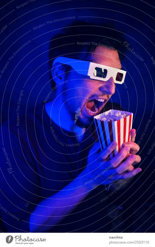 Young crazy man watching a movie Human being Man Dark Adults Lifestyle Funny Style Food Leisure and hobbies Fear Masculine Fresh Culture Authentic Eyeglasses