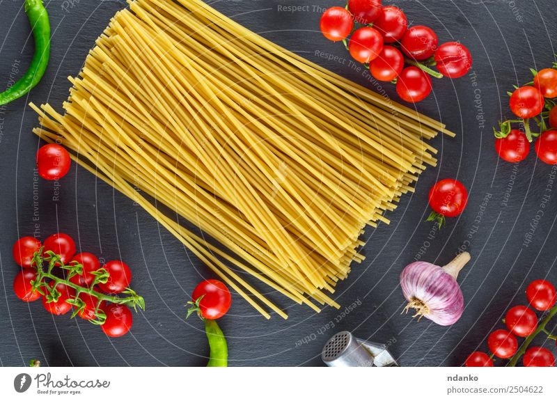 Uncooked pasta spaghetti Vegetable Dough Baked goods Herbs and spices Lunch Eating Fresh Large Long Above Yellow Red Black Colour Tradition Spaghetti food