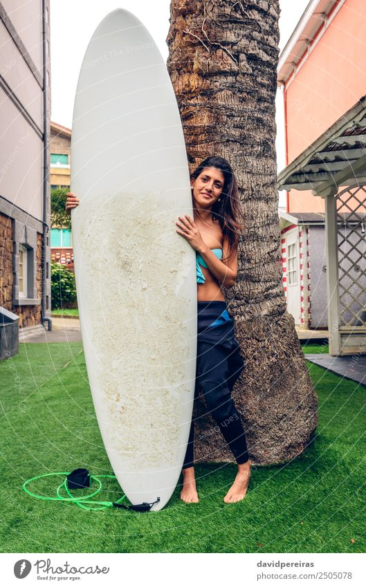 Surfer woman with bikini and wetsuit holding surfboard Woman Human being Vacation & Travel Summer Beautiful Green Tree Eroticism Joy Beach Black Adults
