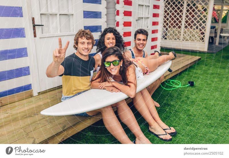 Young friends holding woman on top of surfboard Woman Nature Vacation & Travel Man Summer Beautiful Ocean Joy Beach Adults Lifestyle Sports Laughter Happy