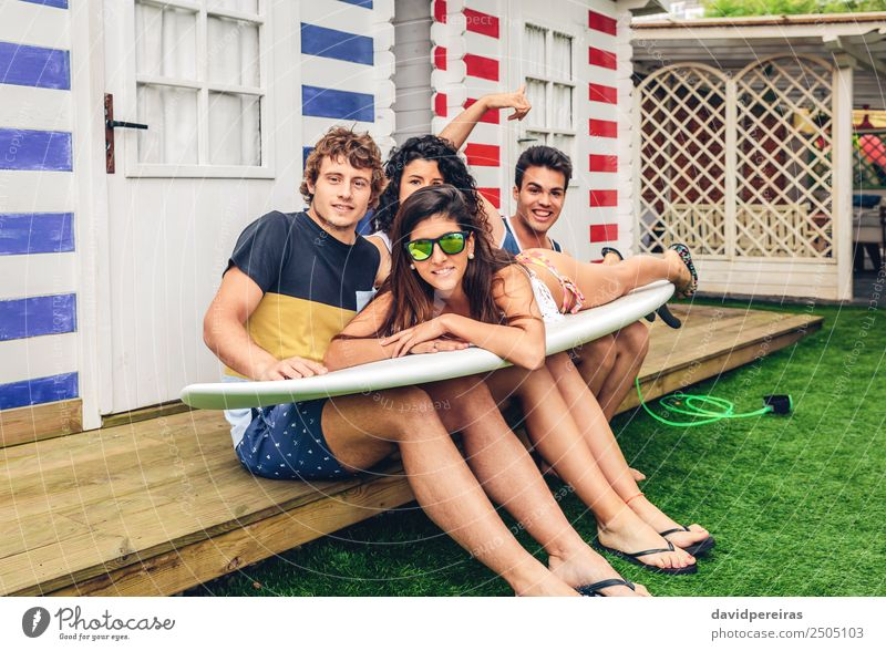 Young friends holding woman on top of surfboard Lifestyle Joy Happy Beautiful Leisure and hobbies Vacation & Travel Summer Beach Ocean Garden Sports Woman