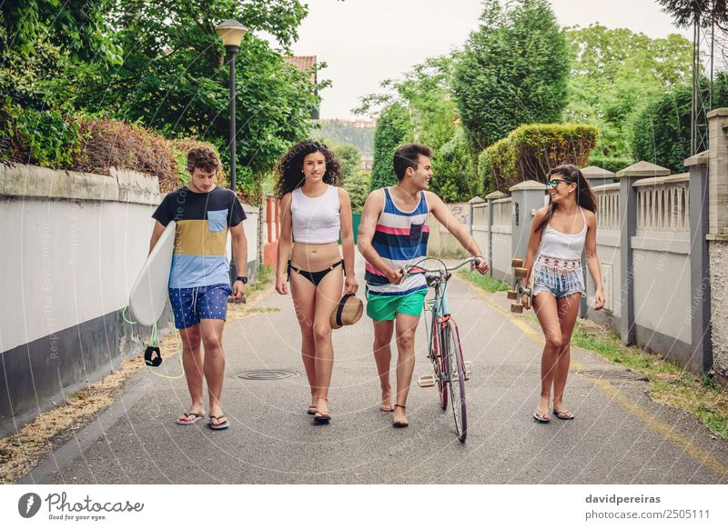 Happy young people walking along road in summer day Lifestyle Joy Relaxation Leisure and hobbies Vacation & Travel Summer Sports Woman Adults Man Friendship