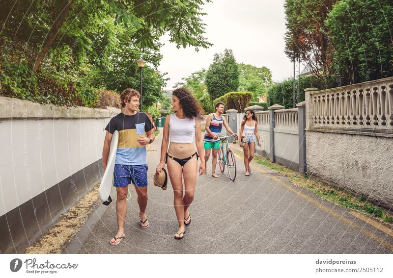 Happy young people walking along road in summer day Lifestyle Joy Leisure and hobbies Vacation & Travel Summer Sports Woman Adults Man Friendship Couple