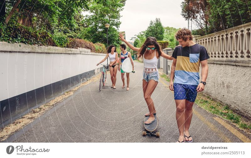 Happy young woman riding on skate with her friends Lifestyle Joy Leisure and hobbies Vacation & Travel Summer Sports Woman Adults Man Friendship Couple