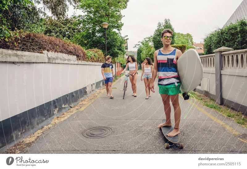 Young man riding on skate and holding surfboard Woman Youth (Young adults) Man Summer Joy Beach Street Adults Lifestyle Sports Laughter Happy Group Copy Space