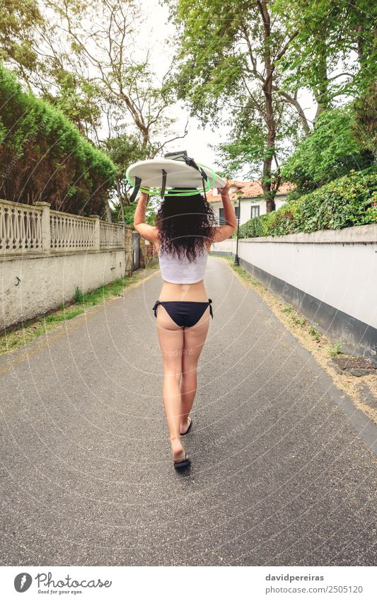 Brunette girl holding surfboard over head and walking Woman Human being Vacation & Travel Summer Beautiful White Ocean Eroticism Joy Beach Black Street Adults