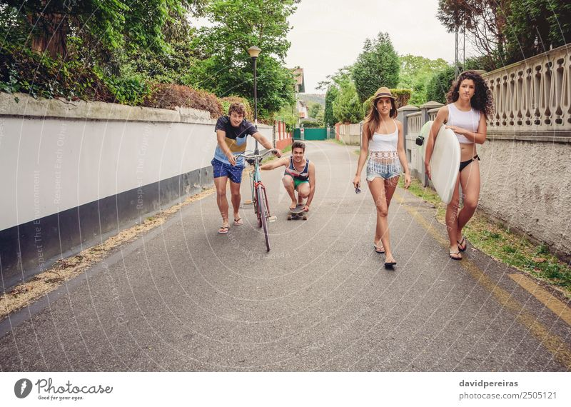 Happy young people having fun with skateboard and bicycle Woman Vacation & Travel Youth (Young adults) Man Summer Relaxation Joy Street Adults Lifestyle Sports