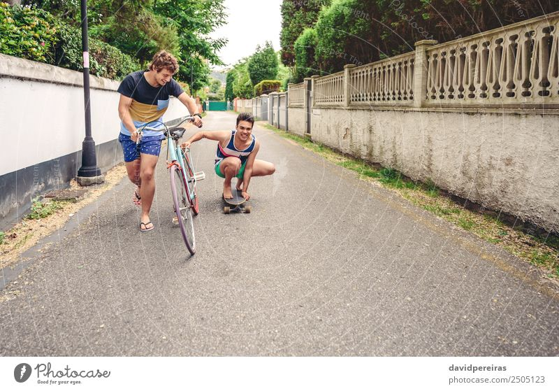 Two men having fun riding bike and skateboard Lifestyle Joy Happy Relaxation Leisure and hobbies Vacation & Travel Summer Sports Man Adults Friendship
