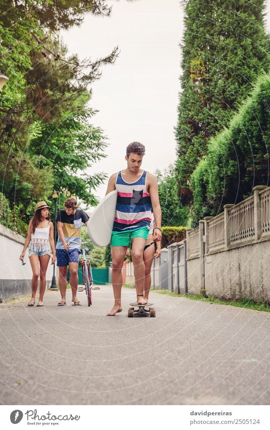 Young man riding on skate and holding surfboard Woman Youth (Young adults) Man Summer Joy Beach Street Adults Lifestyle Sports Laughter Happy Group Together