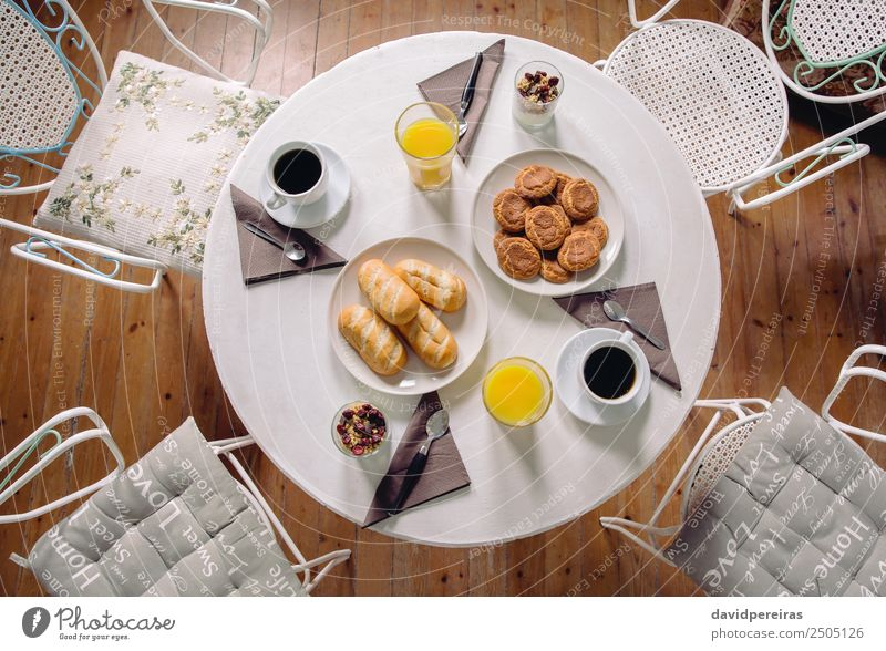 Top view of healthy breakfast served over a table Yoghurt Fruit Croissant Breakfast Juice Coffee Plate Bowl Spoon Table Restaurant Fresh Hot Delicious Above