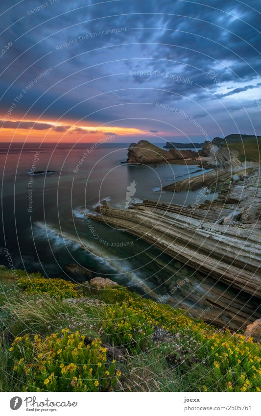 Rocky cliff with sunset on the horizon steep coast steep slope Dusk Deep depth of field Nature Wide angle Brown Blue Colour photo Water Day Exterior shot