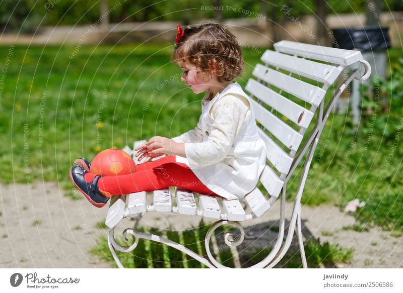 Adorable little girl playing with a ball sitting on a park bench Lifestyle Joy Happy Beautiful Face Summer Child Human being Toddler Girl Woman Adults Infancy 1