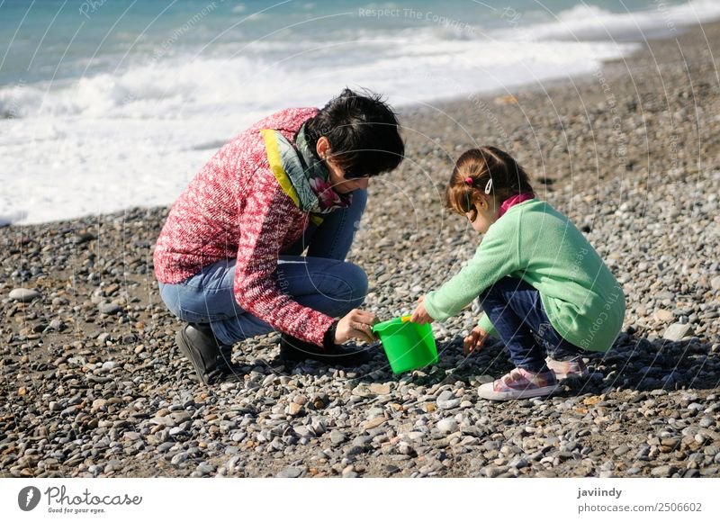 Mother and little daughter having fun on the beach in winter Woman Child Human being Nature Vacation & Travel Youth (Young adults) Young woman Girl Winter Beach