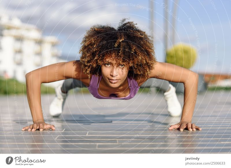 Black fit woman doing pushups on urban floor Lifestyle Body Hair and hairstyles Leisure and hobbies Sports Work and employment Young woman Youth (Young adults)