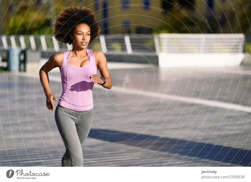 Black woman afro hairstyle running outdoors in urban road Lifestyle Beautiful Hair and hairstyles Wellness Leisure and hobbies Sports Jogging Human being