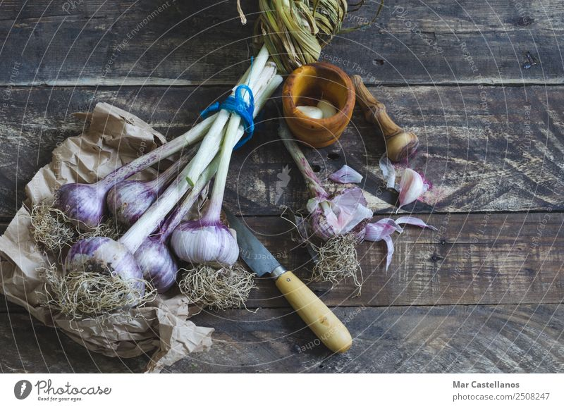 Bunch of garlic with kitchenware on wooden background Nature Summer Plant Green Eating Healthy Natural Brown Nutrition Fresh Herbs and spices Kitchen Violet