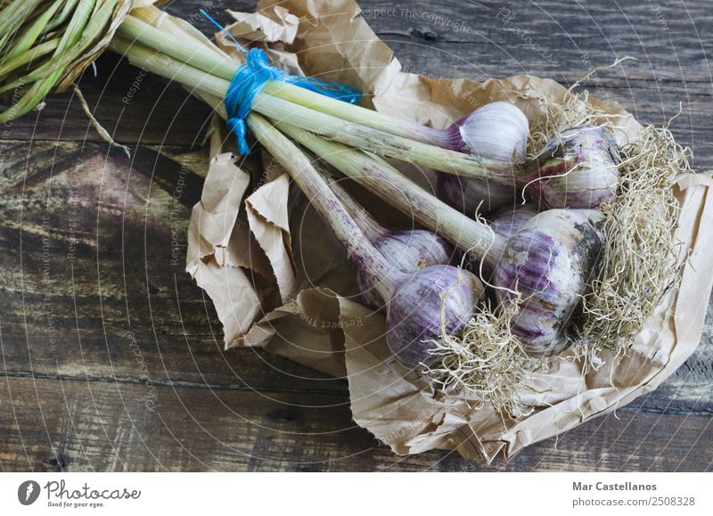 Natural garlics on wooden background Nature Summer Plant Green Eating Brown Nutrition Fresh Paper Herbs and spices Kitchen Agriculture Violet Vegetable