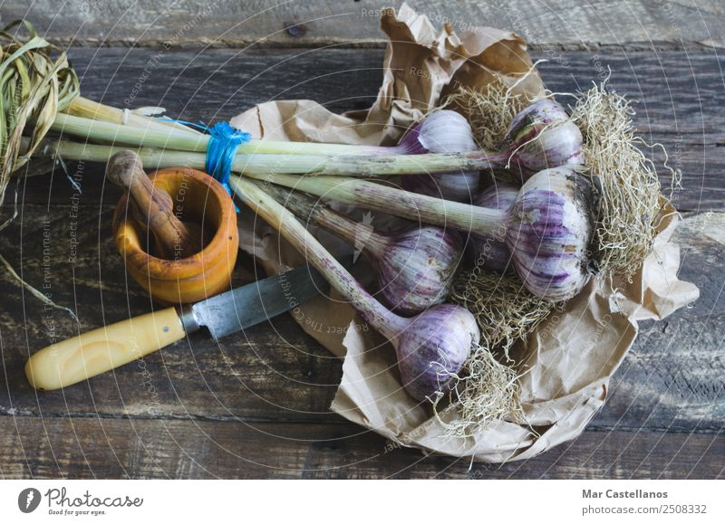 Bunch of garlic with kitchenware on wooden background Nature Summer Plant Green Leaf Eating Yellow Natural Wood Brown Nutrition Fresh Herbs and spices Kitchen