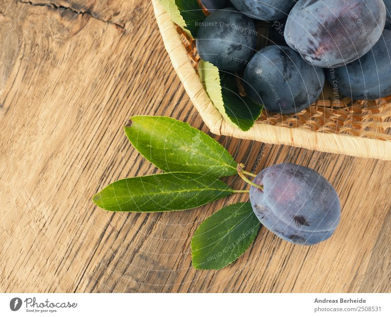 Freshly harvested organic plums in a basket on a wooden table Food Fruit Dessert Organic produce Vegetarian diet Healthy Eating Summer Nature Delicious Sweet