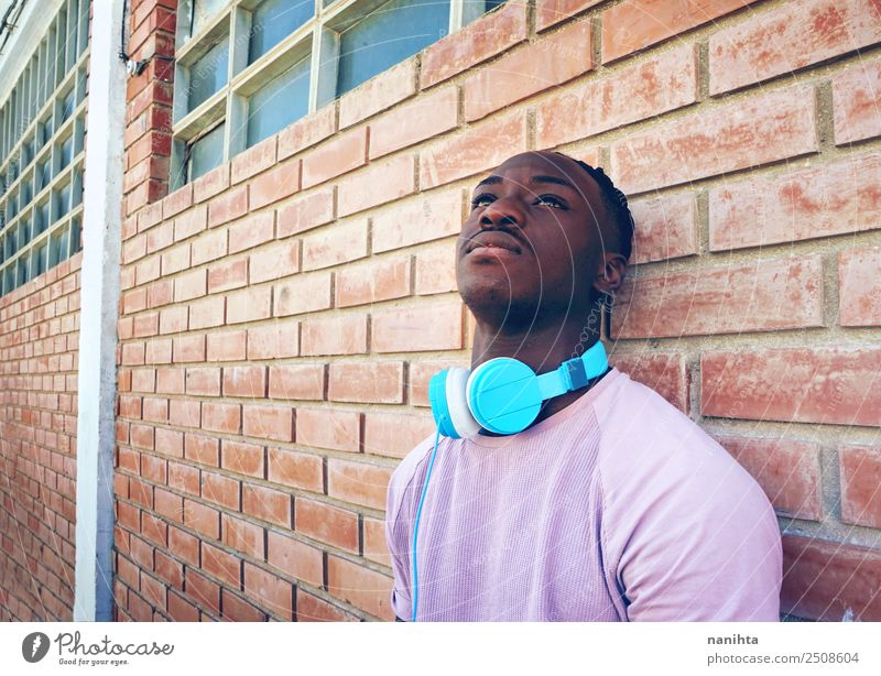 Young black man against a brick wall Lifestyle Style Design Senses Relaxation Leisure and hobbies Headset Headphones Technology Entertainment electronics