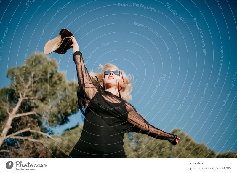 Happy blonde woman raising the arm with a hat in the hand at the forest during sunset. Woman Forest Sunglasses Peoples Nature Caucasian Vacation & Travel