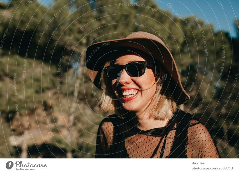 Portrait of blonde woman with hat and sunglasses having fun in nature at sunset. Lifestyle Style Joy Beautiful Wellness Well-being Vacation & Travel Freedom