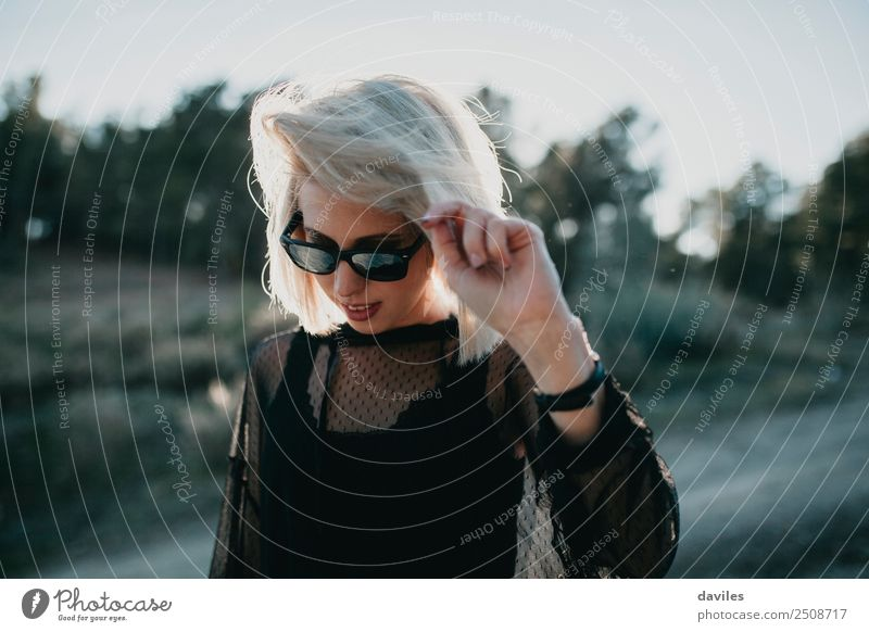 Blonde girl with sunglasses and black dress walking in nature with backlight Lifestyle Elegant Style Joy Vacation & Travel Trip Adventure Sun Human being