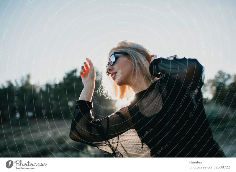 Blonde woman with black dress and sunglasses performing dance in nature with backlight Lifestyle Elegant Style Joy Beautiful Wellness Harmonious Well-being Sun