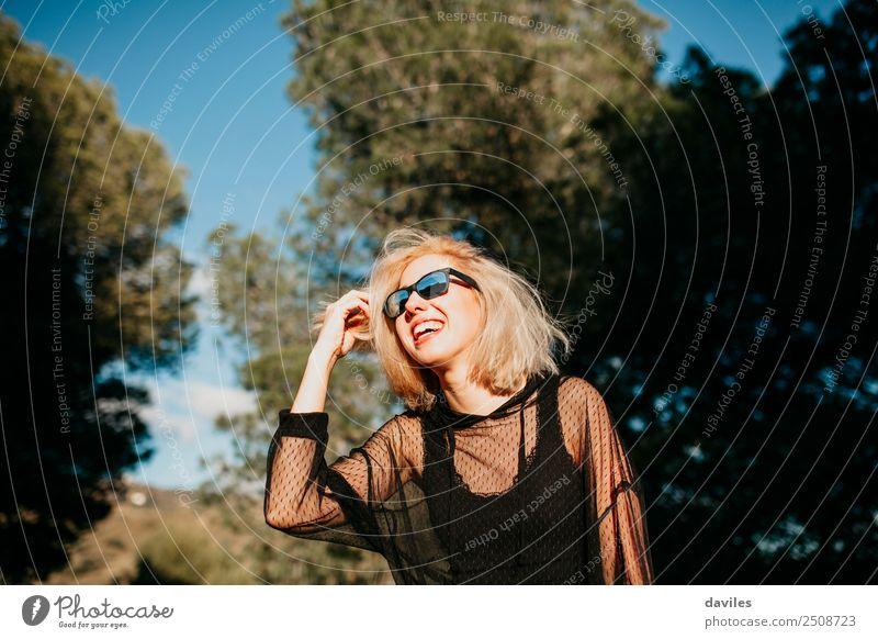 Cool blonde woman with sunglasses and black dress having fun in nature during sunset. Lifestyle Elegant Joy Happy Beautiful Wellness Sun Human being Feminine