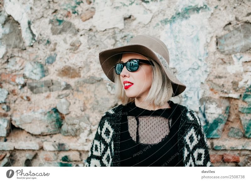 Portrait of blonde girl with hat and sunglasses looking away with a stone wall in the background. Lifestyle Shopping Luxury Elegant Style Joy Beautiful Face