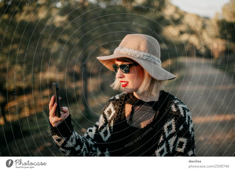 Blonde young woman with hat and sunglasses taking a photo with a mobile phone in the forest at sunset. Lifestyle Elegant Style Relaxation Telephone Cellphone