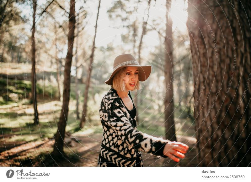 Woman walking in the forest at sunset and reaching a tree trunk with the hand. Lifestyle Joy Leisure and hobbies Sun Human being Feminine Young woman