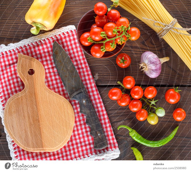 cutting board with a knife Vegetable Dough Baked goods Knives Wood Fresh Large Long Above Brown Yellow Red Black Colour Tradition Spaghetti pasta food Tomato