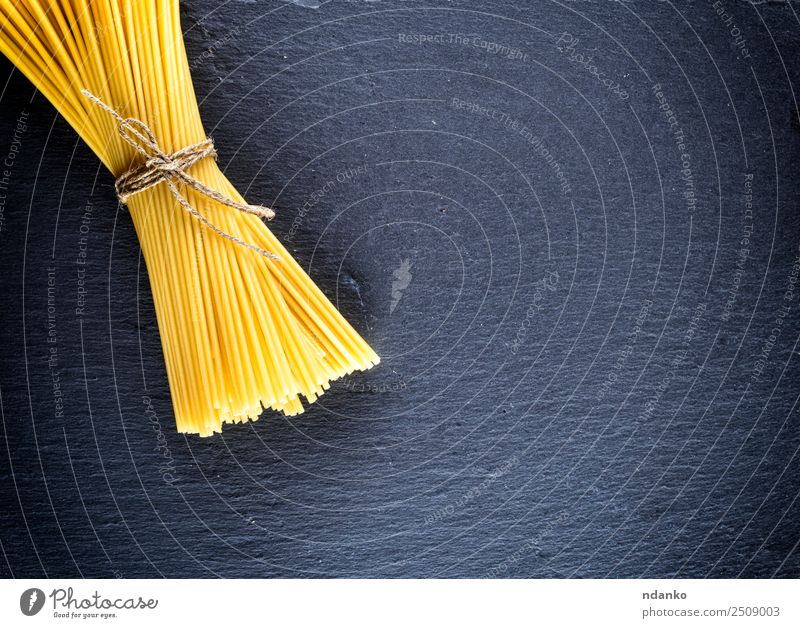 spaghetti tied with a rope Dough Baked goods Lunch Rope Line Fresh Large Long Above Yellow Black Colour Tradition Spaghetti pasta food background Raw Italian