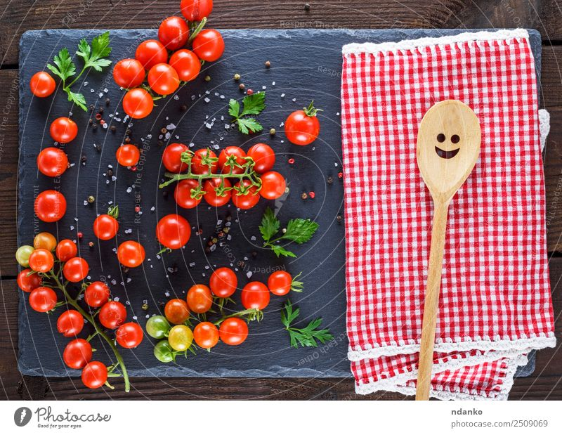 red tomatoes on a black board Vegetable Herbs and spices Nutrition Vegetarian diet Diet Spoon Summer Kitchen Nature Wood Fresh Small Natural Above Juicy Green
