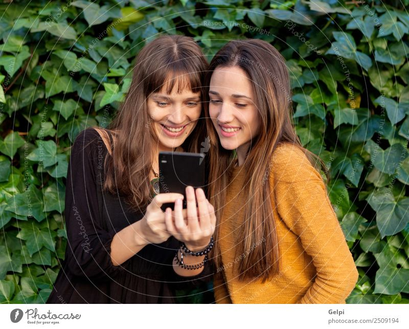 Nice sisters with blue eyes Lifestyle Joy Happy Beautiful Playing Telephone Cellphone PDA Technology Internet Woman Adults Sister Friendship