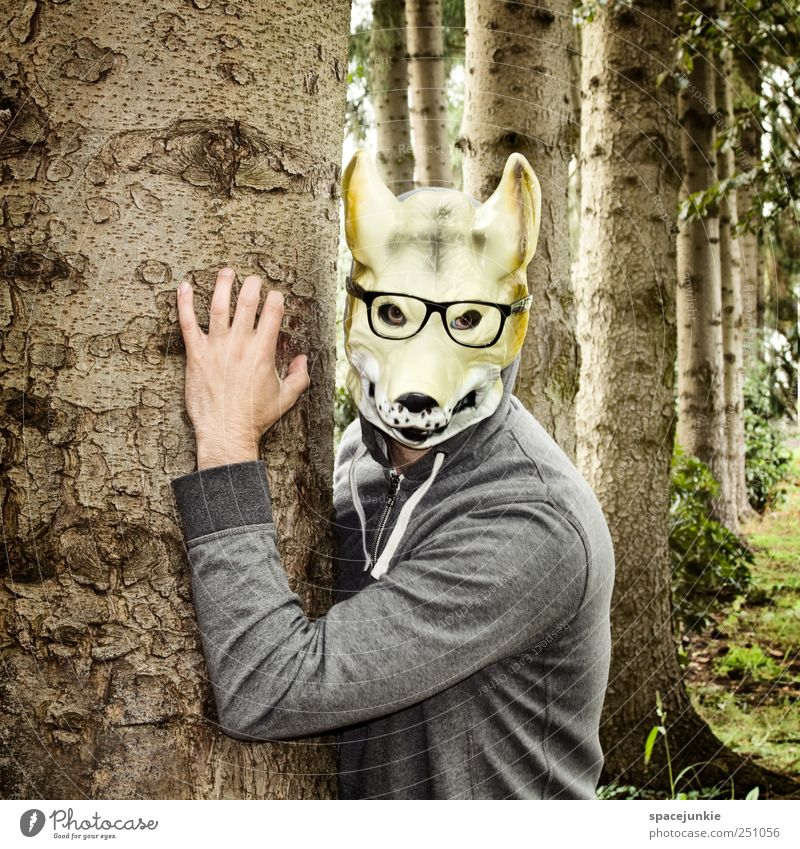 The man with the wolf mask Human being Man Adults 1 Environment Nature Beautiful weather Tree Grass Bushes Garden Forest Observe Brown Evil Wolf Animal face